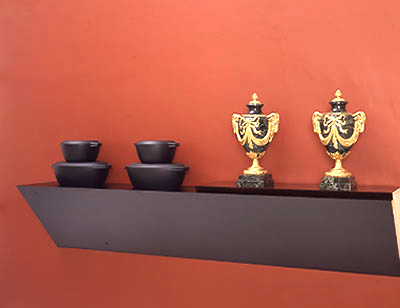 "Haim Steinbach, sweetest taboo, 1987, plastic-laminated wood shelf, marble-and-brass urns, and cast-iron cookware, 37 1/2 x 95 x 15 1/2""."