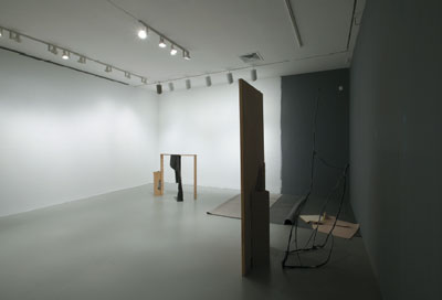"View of ""Day for Night,"" 2006, Whitney Museum of American Art, New York. Background, left, and foreground: Gedi Sibony, Their Proper Places the Entities from Which Partial Aspects Emerge, 2006, wood, branches, door, and garbage bag. Background, right: Gedi Sibony, Neither Attentive Nor Inattentive, 2006, carpet."