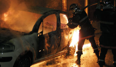 Firefighters extinguishing a car fire set by protesters, Argenteuil, France, November 2005. Photo: AP/Michel Spingler.