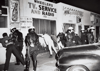 Police searching neighborhood residents during an outbreak of unrest in Watts, Los Angeles, March 15, 1966. Photo: Bettmann/Corbis.