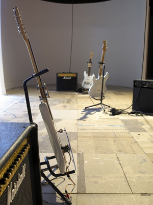 Saâdane Afif, Power Chords, 2005, 11 electric guitars, 11 amplifiers, 11 automatons, Apple computer, and software. Installation view, Lyon Biennale, 2005.