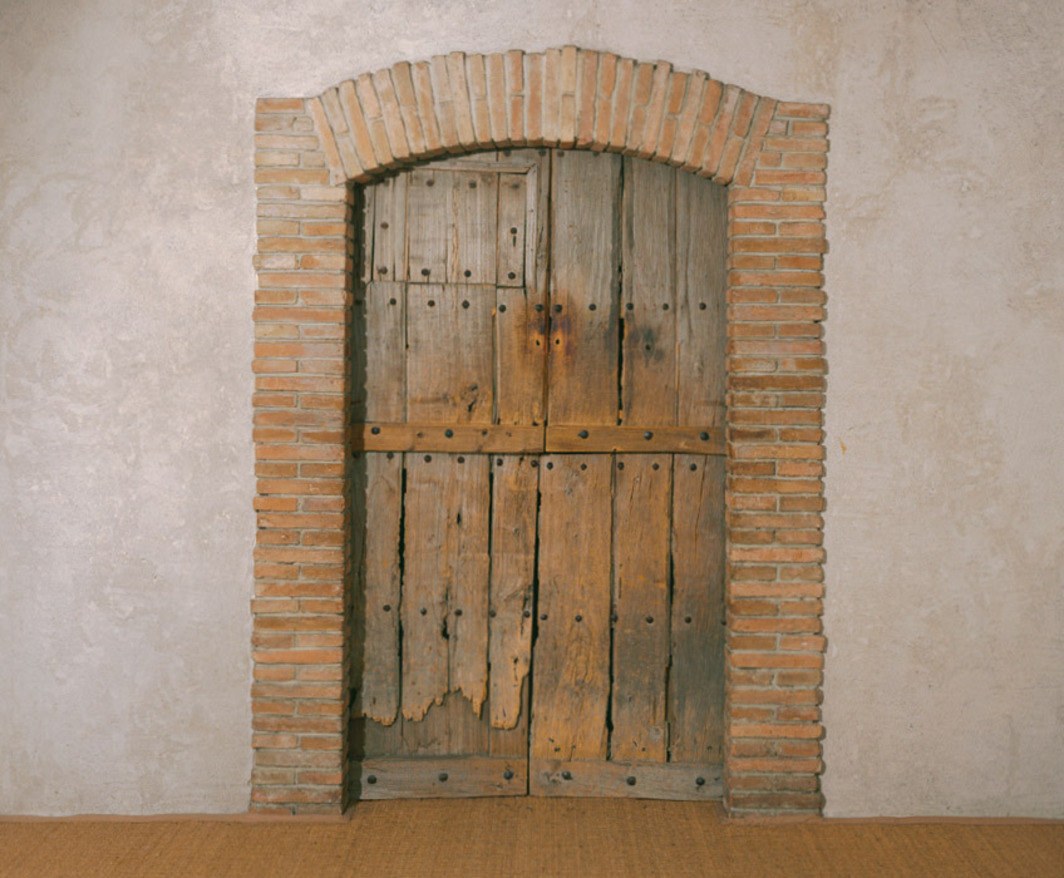 "Marcel Duchamp, Étant donnés: 1º la chute d'eau, 2º le gaz d'éclairage . . . (Given: 1. The Waterfall, 2. The Illuminating Gas . . .), 1946–66, wooden door, bricks, velvet, wood, leather, metal armature, twigs, aluminum, iron, glass, Plexiglas, linoleum, cotton, electric lights, gas lamp, motor, 95 1⁄2 x 70 x 49"". Exterior view. © 2010 Estate of Marcel Duchamp/Artists Rights Society (ARS), New York/ADAGP, Paris."