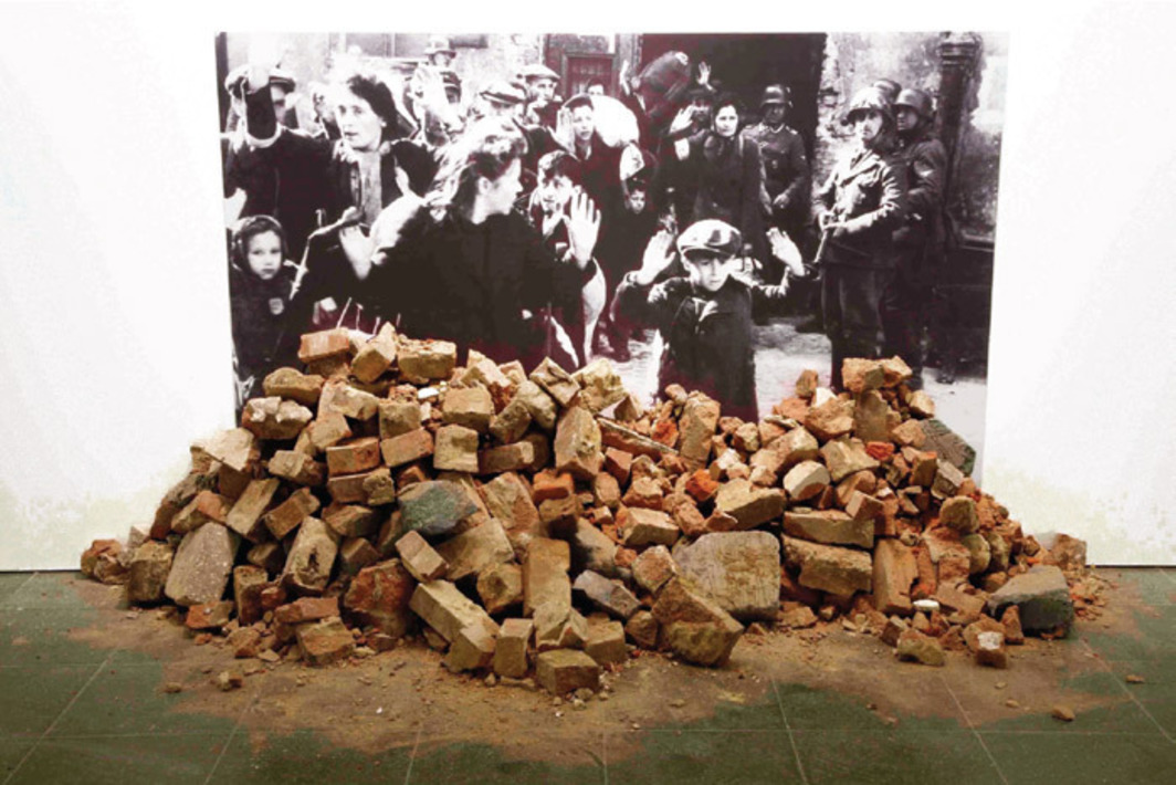 "Gustav Metzger, Historic Photographs: No. 1: Liquidation of the Warsaw Ghetto, April 19—28 days, 1943, 1995/2009, black-and-white photograph mounted on Foamex board, rubble. From the series ""Historic Photographs,"" 1990–. Installation view, Serpentine Gallery, London. Photo: Jerry Hardman-Jones."