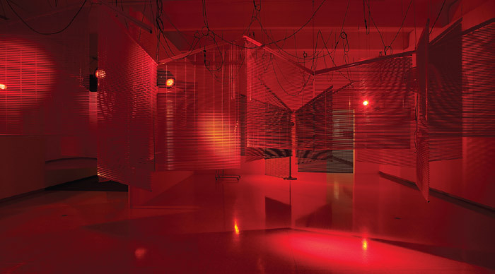 Haegue Yang, Yearning Melancholy Red, 2008, venetian blinds, mirror, moving lights, three sets of infrared heaters, fans, drum set, cables. Installation view, Walker Art Center, Minneapolis, 2010.