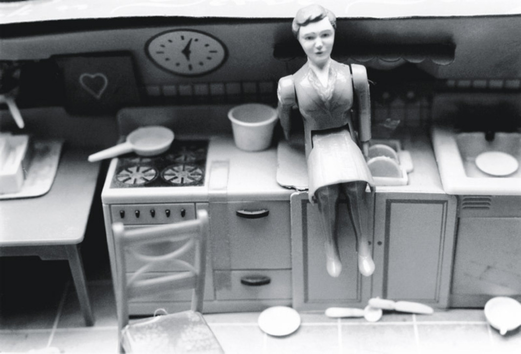 "Laurie Simmons, Woman/Kitchen/Sitting on Sink, 1976, black-and-white photograph, 5 1/4 x 8""."