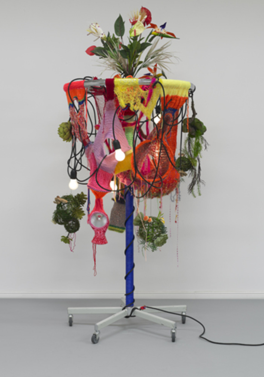 "Haegue Yang, Female Natives, 2010, grey single shaft clothing rack on casters with round top, light bulbs (frosted), cable, artificial plants, knitting yarn, cord, metal ring, metal chain, aluminum reflector, 37 1/2 x 82 2/3""."
