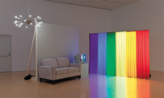 William Leavitt, Spectral Analysis, 1977/2010, sofa, starburst light fixture, end table, television with DVD of rotating prism, wooden wall, curtain panel, six ceiling-mounted theatrical lights with gels, recorded highway-traffic sounds, dimensions variable.