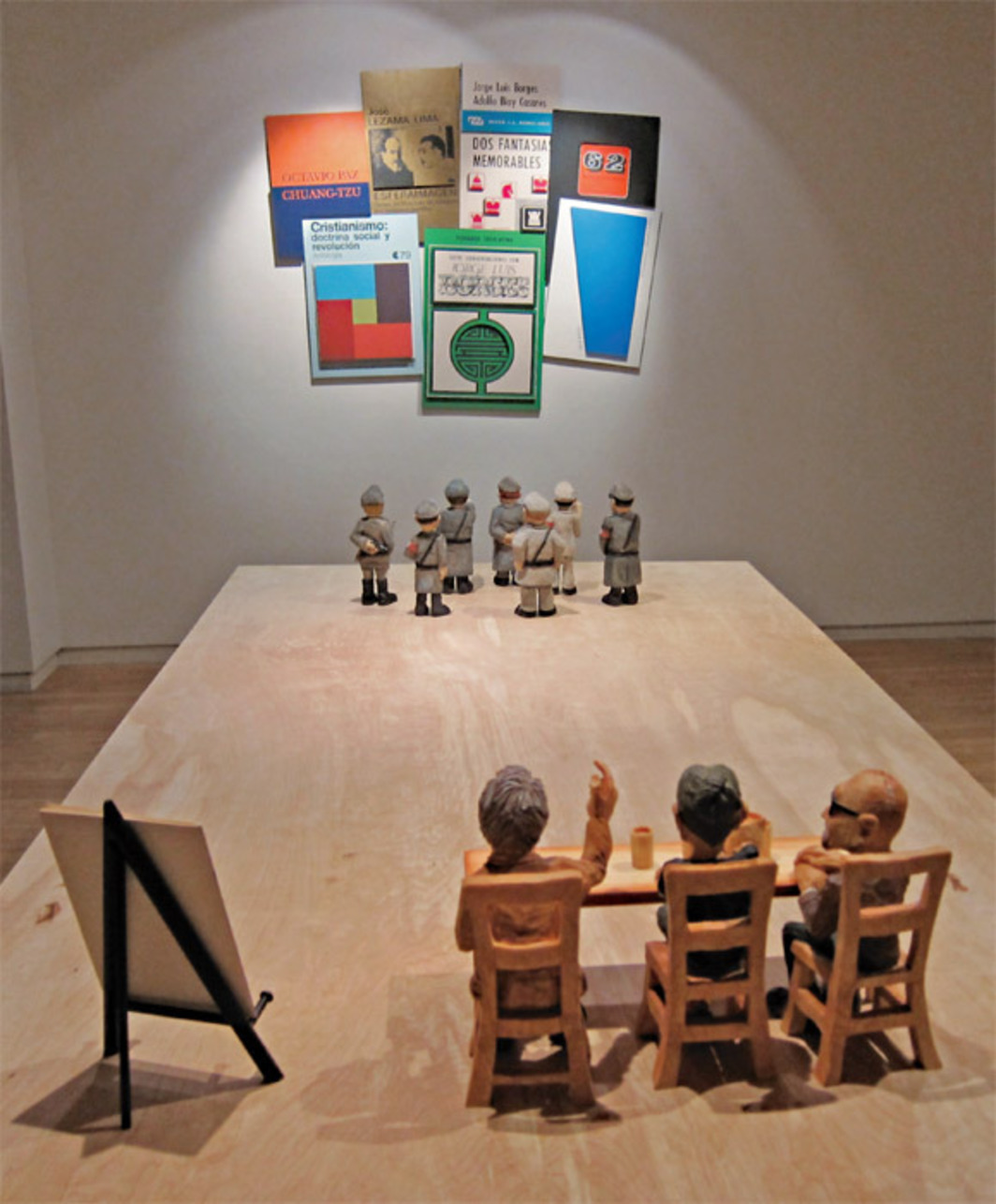 Nicolás Guagnini, The Panel Discussion, the Tennis Match, and a Bodegón, 2011, oil on shaped aluminum composite panel, carved wooden figures, miniature easel with facsimile catalogue, plywood table, twenty-second audio loop. Installation views, Andrew Roth, New York.
