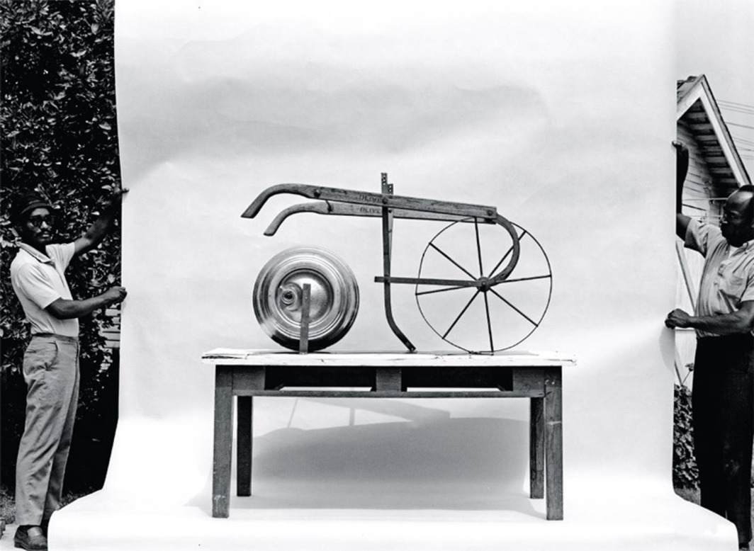 "Judson Powell and Noah Purifoy, Barrel and Plow, 1966, beer barrel and plow mounted on table. Documentary photograph of the work with Darcy Robinson and Judson Powell, Los Angeles, 1966. Barrel and Plow was one of fifty works included in the 1966 exhibition ""66 Signs of Neon."" Photo: Harry Drinkwater."
