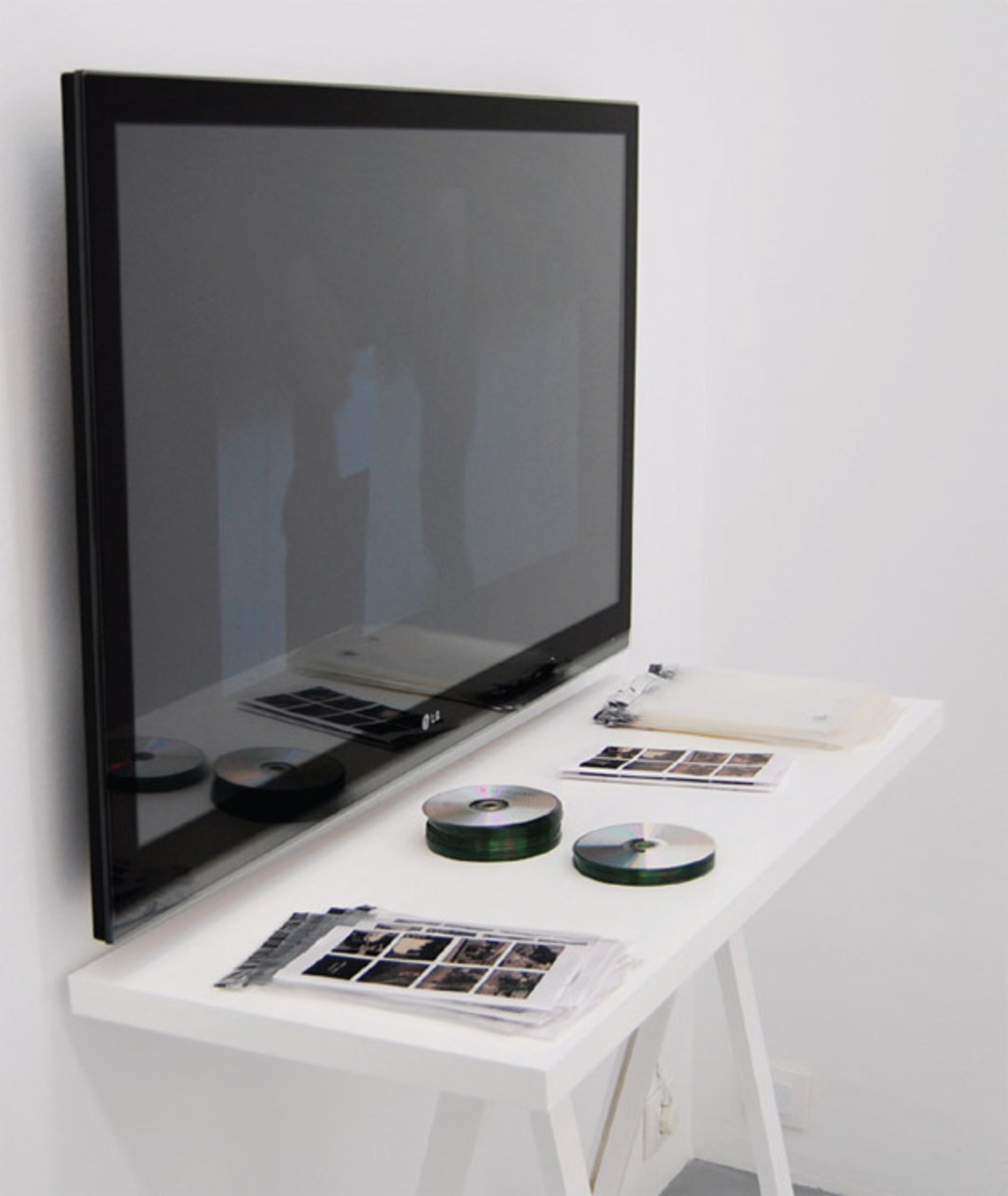 Pedro G. Romero, Archivo F.X.—L'Argent (Archive F.X.—Money), 2010, DVD, monitor, blank DVDs, plastic envelopes, covers. Installation view.