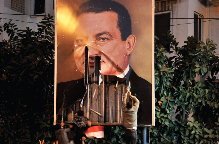 Demonstrators deface a poster of Hosni Mubarak, Alexandria, Egypt, January 25, 2011. Photo: AP.