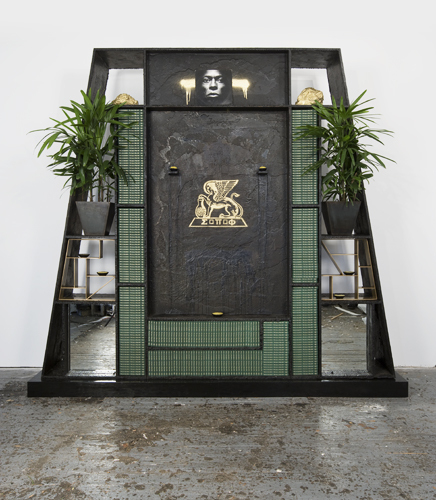 "Rashid Johnson, Souls of Black Folk, 2010, black soap, wax, books, vinyl, brass, shea butter, plants, space rocks, mirrors, gold paint, stained wood, 9' 6"" x 10' 4 3/4"" x 2' 3/8""."