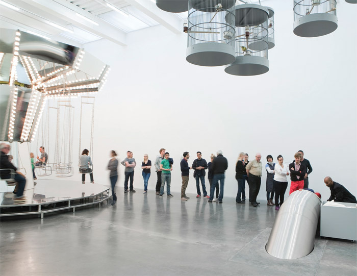 "View of ""Carsten Höller: Experience,"" 2011, New Museum, New York. From left: Minor Carousel, 2005; Singing Canaries Mobile, 2009; Untitled (Slide), 2011. Photo: Benoit Pailley."