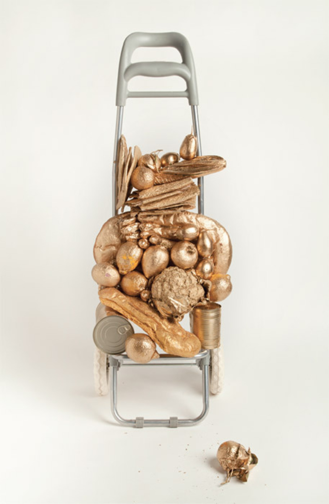 "Liz Glynn, Kreutzberg Hoard, 2011, shopping cart armature, produce, gold leaf, acrylic, 36 x 12 x 10""."