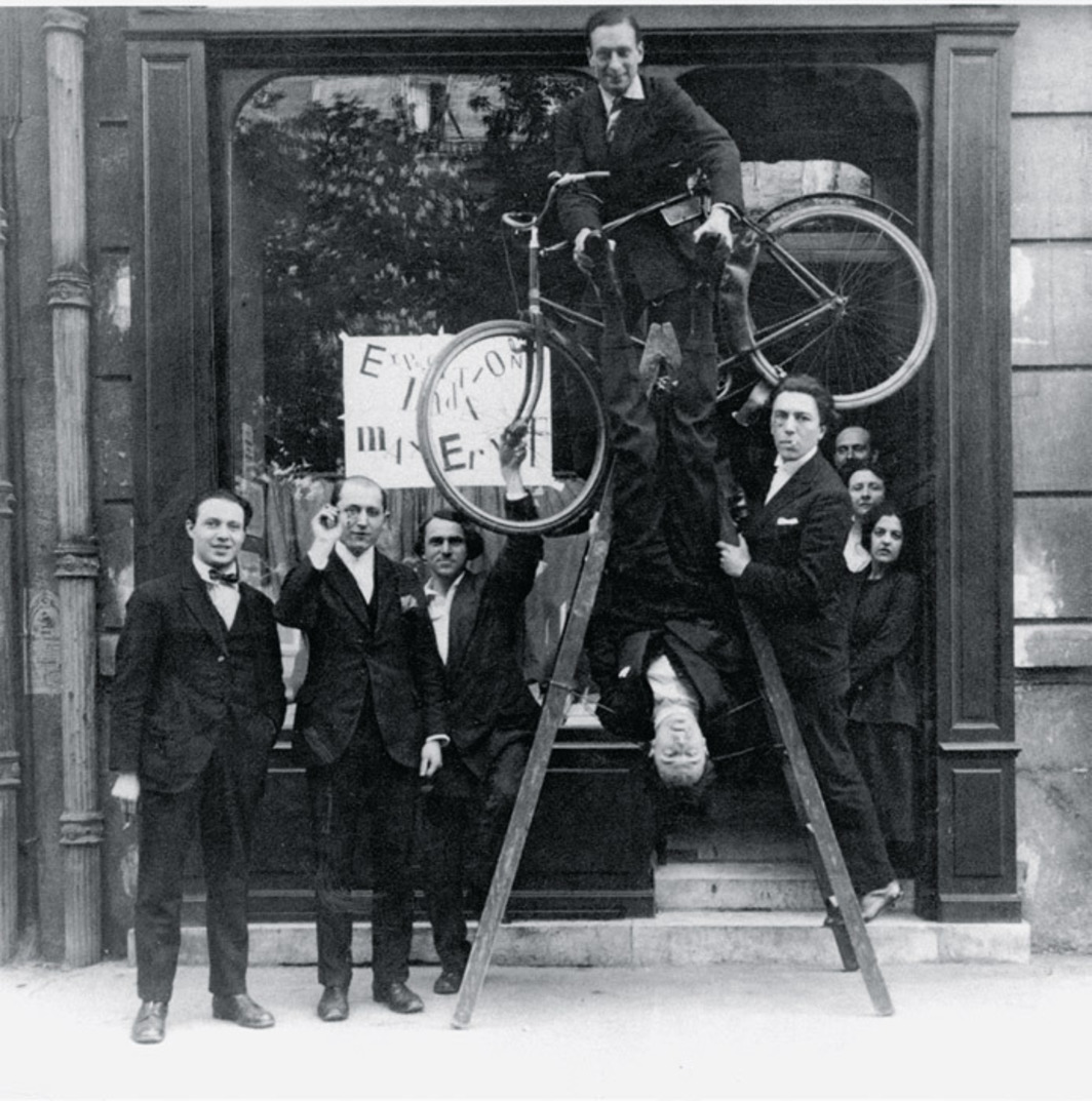 "René Hilsum, Benjamin Péret, Serge Charchoune, Philippe Soupault (with bicycle), Jacques Rigaut (upside down), and André Breton at the opening of ""Dada Max Ernst,"" Galerie Au Sans Pareil, Paris, May 2, 1921."
