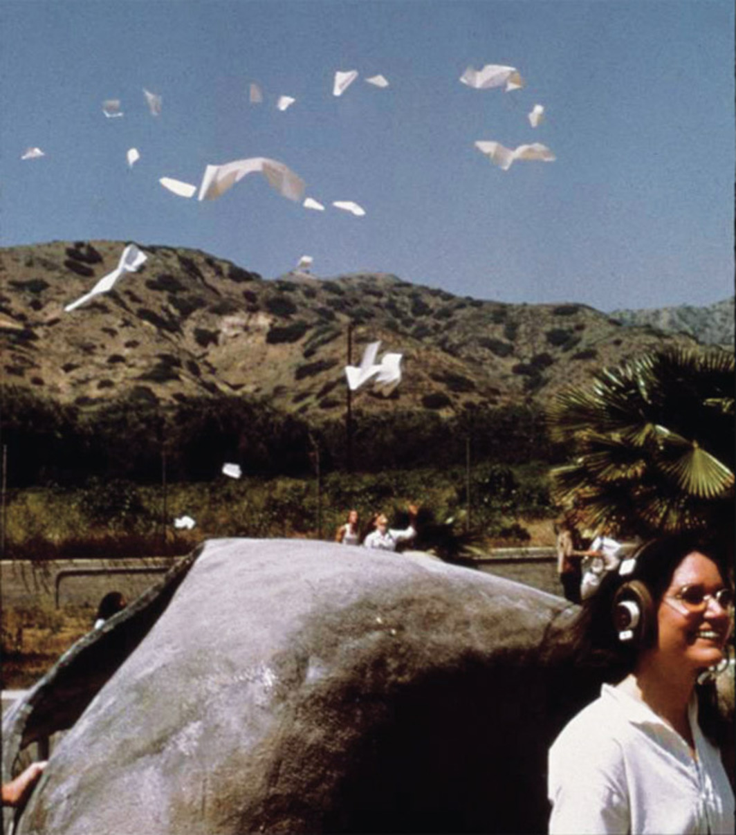 Alison Knowles (in collaboration with CalArts students Norman Kaplan and Richard Banks), Poem Drop, 1971. Performance view, CalArts campus, Burbank, CA, 1971. Foreground: Knowles in front of House of Dust, 1968.