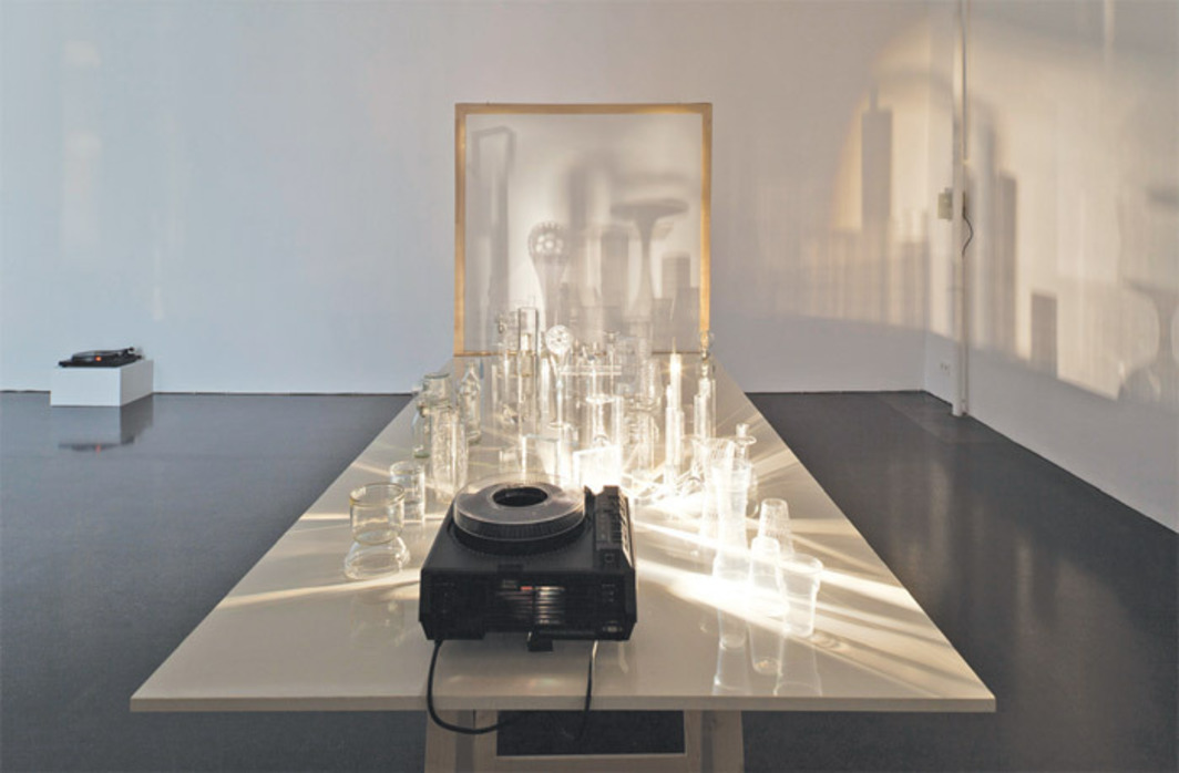 "Michaela Melián, Lunapark, 2012, slide projector, record player, slide, glass objects, motor, particle board, stretcher frame with rear projection foil, with sound, 106 1/4 x 47 1/4 x 76 3/4""."