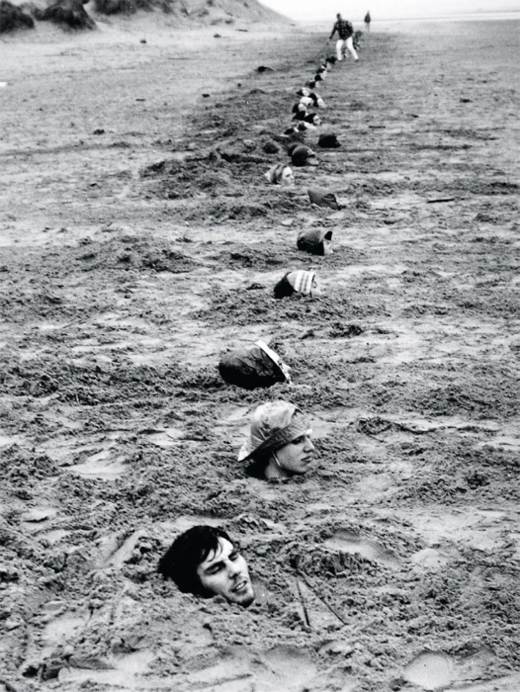 "Keith Arnatt, Liverpool Beach Burial, 1968, gelatin silver print, 10 1/4 x 7 1/8"". From ""Ends of the Earth: Land Art to 1974."""