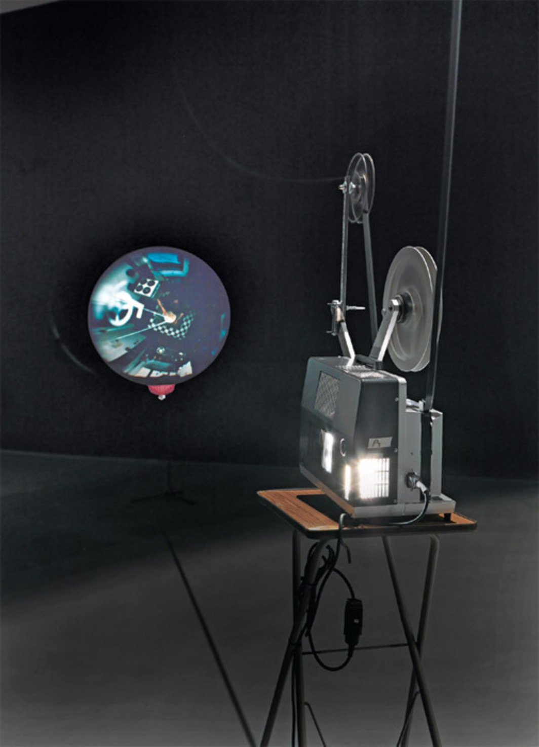 Klaus Lutz, Vulcan, 2004, 16-mm film, projector, balloon, salad strainer, music stand, sound, 2 minutes. Installation view.