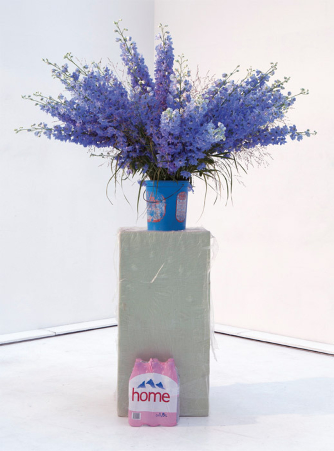 "Heike-Karin Föll, Delphinium-Bouquet and Elaine Scarry, 2012, foam, plastic sheet, pack of Evian bottles, plastic bucket, water, wire, fresh delphiniums, 70 7/8 x 31 1/2 x 31 1/2""."