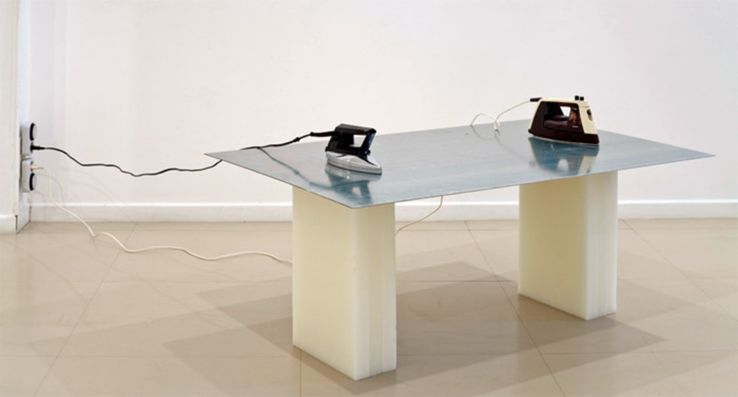 "Nuria Fuster, Esculpidoras II (Sculptresses II), 2012, metal, wax, two irons, 27 1/2 x 47 1/4 x 28 3/4"". From the series ""Accidentes"" (Accidents), 2011–."
