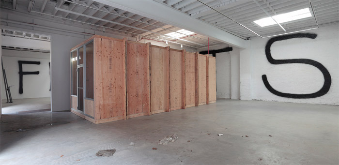 "View of ""Rirkrit Tiravanija."" Wall text: untitled 2011. Plywood structure: untitled 2011."