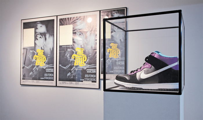 "View of ""Scott Benzel,"" 2011. Foreground: Counterfeit Nike ""Heaven's Gate"" SB Dunks, 2011. Background: Original posters for The Trip (1967) with original stickers, 2011."