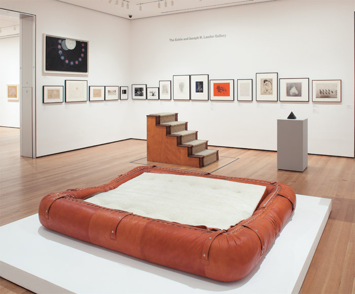 "View of ""Artist's Choice: Trisha Donnelly,"" 2012–13, Museum of Modern Art, New York. Foreground: Alessandro Becchi, Anfibio Convertible Couch, 1971. Background, from left: Joe Goode, Shoes, Shoes, Shoes, 1966; Michael Lax, Modulion 10 Ionizer, 1980. Wall, top left: František Kupka, The First Step, ca. 1910, oil on canvas, 32 3/4 x 51"". Photo: Thomas Griesel."