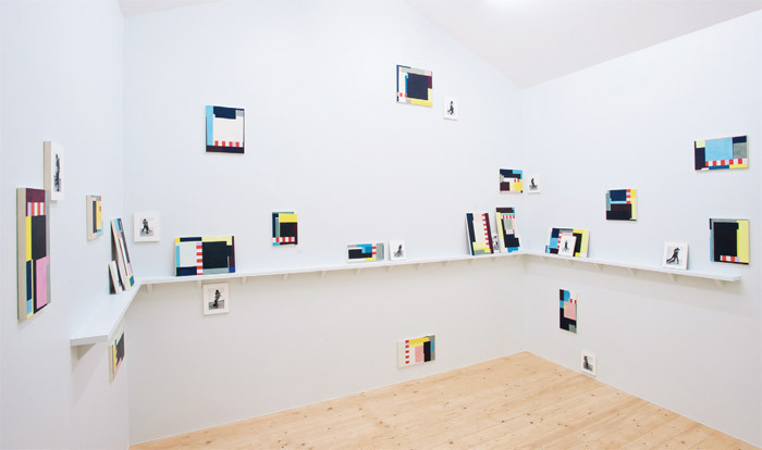 Doug Ashford, Many Readers of One Event, 2012, eighteen tempera paintings on wood and eleven ink-jet prints on wooden shelf, hut. Installation view, Karlsaue Park, Kassel. From Documenta 13. Photo: Nils Klinger.