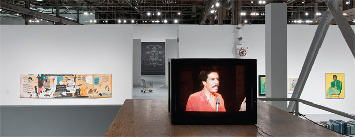 "View of ""Blues for Smoke,"" 2012–13. From left: Jean-Michel Basquiat, Undiscovered Genius of the Mississippi Delta, 1983; Kori Newkirk, Yall (detail), 2012; Kira Lynn Harris, But not the kind that's Blue (detail), 2012; Richard Pryor, Richard Pryor Live in Concert, 1979; Beauford Delaney, Portrait of a Young Musician, n.d. Photo: Brian Forrest."