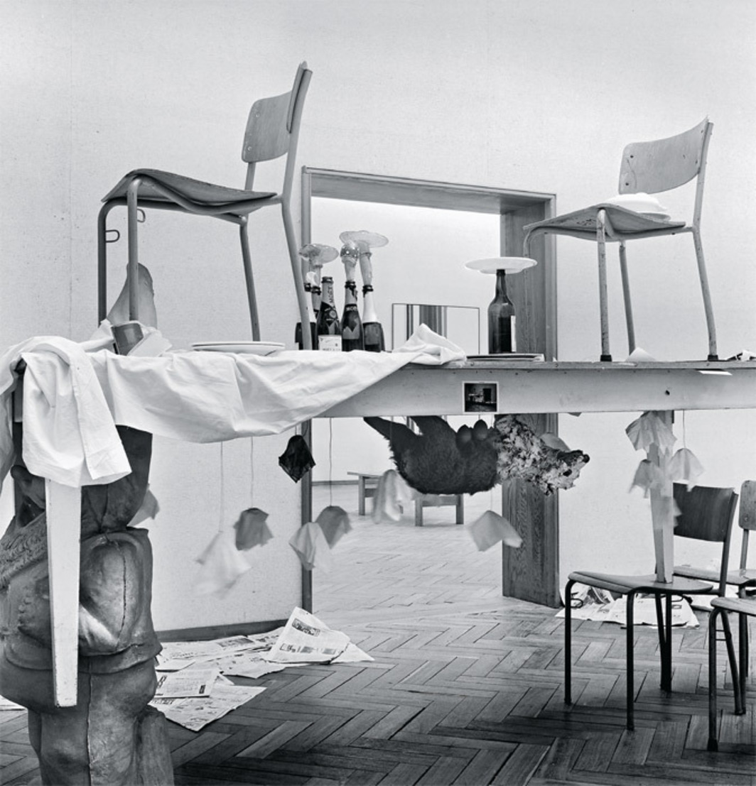 "Paul Thek, Untitled (Dwarf Parade Table), 1969, wood, plaster, eggs, photographs, drawings, plastic, ceramic plates, glass, metal, gum, latex, paint, taxidermic dog, fabric, chairs, 34 1/2 x 92 1/2 x 29 3/4"". Installation view, Stedelijk Museum, Amsterdam."
