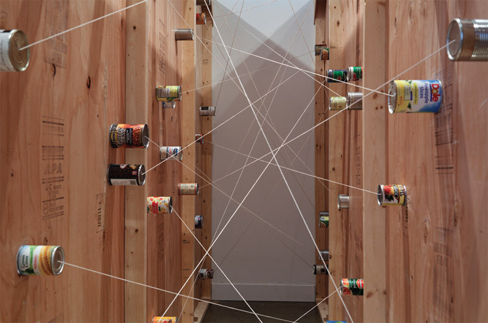 Amalia Pica, If These Walls Could Talk (with door) (detail), 2011, wood, tin cans, screws, paint, glue, string. Installation view.