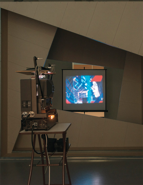 David Maljković, Images with Their Own Shadows, 2008, projector, stand, screen, metal studs, plasterboard, 16-mm film (color, sound, 6 minutes 16 seconds). Installation view.