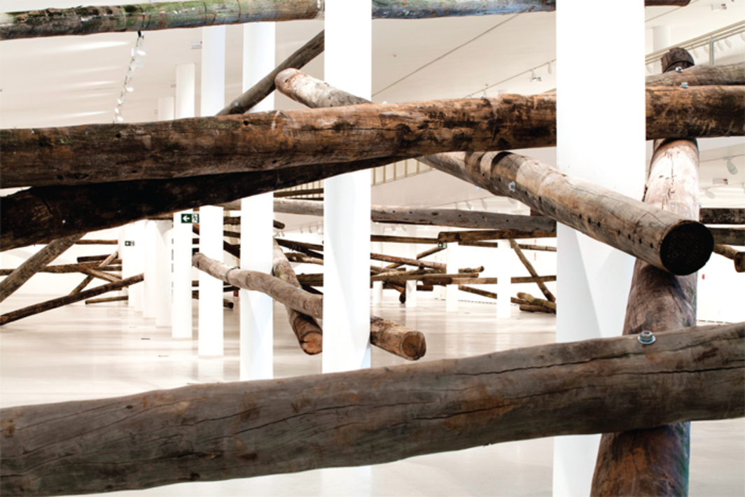 Carlito Carvalhosa, Sala de Espera (Waiting Room), 2013, telephone poles, steel bolts. Installation view, Museu de Arte Contemporânea, São Paulo.