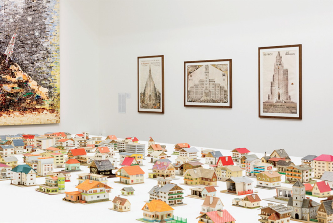 "View of ""The Encyclopedic Palace,"" 2013, Central Pavilion, Venice. Foreground: Oliver Croy and Oliver Elser, The 387 Houses of Peter Fritz (1916–1992), Insurance Clerk from Vienna, 1993–2008. Background, from left: Jack Whitten, 9-11-01, 2006; Achilles Rizzoli, Irwin Peter Sicotte Jr. Symbolically Delineated/The ""Sayanpeau,"" 1936; Achilles Rizzoli, Alfredo Capobianco and Family Symbolically Sketched/Palazzo Del Capobianco, 1937; Achilles Rizzoli, Mr. and Mrs. Harold Healy Symbolically Sketched First Prize, First Anniversary, 1936. Photo: Kate Lacey."