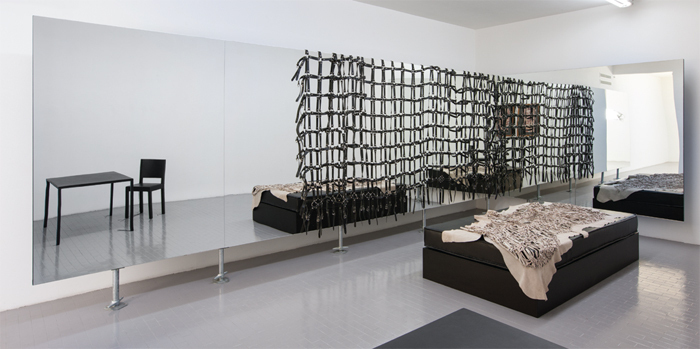 "View of ""Monica Bonvicini,"" 2013. Against wall: Straps & Mirror, 2010. On floor: Black You, 2010."