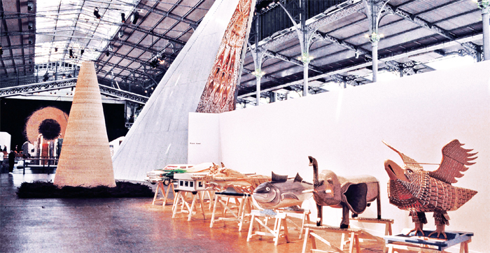 "View of ""Magiciens de la Terre,"" 1989, Grand Halle de La Villette, Paris. Foreground: Kane Kwei, seven coffins (Eagle, Elephant, Fish, Lobster, House, Onion, Mercedes), all 1988. Midground left: Mario Merz, Untitled, 1989. Midground right: Nera Jambruck, Fronton de maison des hommes (Pediment of the House of Men), 1988. Rear wall: Richard Long, Red Earth Circle, 1989. In front of Red Earth Circle: Claes Oldenberg, From the Entropic Library, 1989."