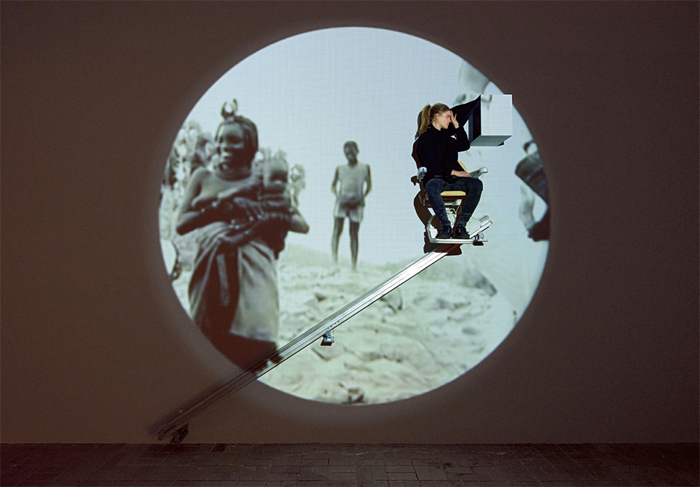 Christoph Schlingensief, The African Twin Towers: Stairlift to Heaven, 2007, stairlift, digital video projection (color, sound, 29 minutes 20 seconds). Installation view.
