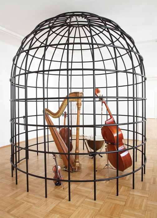 "Daniel Knorr, Block, 2014, violin, cello, double bass, harp, timpani, flute, iron cage, chain, padlock, 11' 5 3/4"" x 9' 10"" x 9' 10""."