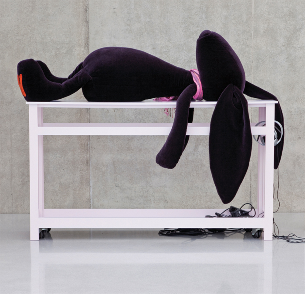 Cosima von Bonin, THE BONIN/OSWALD EMPIRE'S NOTHING #4 (CVB'S PURPLE KIKOY SLOTH RABBIT ON PINK TABLE & MVO'S KIKOY SONG), 2010, fabric, varnished-wood table, wheels, DVD-R, dimensions variable. Photo: Markus Tretter.