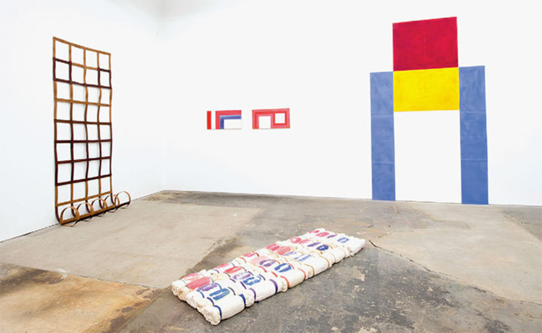 "View of ""Supports/Surfaces,"" 2014. From left: Daniel Dezeuze, Echelle de bois souple (Flexible Wood Ladder), 1974; Marc Devade, Untitled, 1967; Marc Devade, Untitled, 1967; Louis Cane, Toile découpée (Cut-Out Canvas), 1970. Floor: Patrick Saytour, Untitled, 1974."