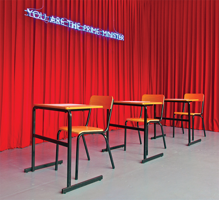 Karen Mirza and Brad Butler, You Are the Prime Minister (neon sign), 2014, curtain, desk, chairs, neon. Installation view.