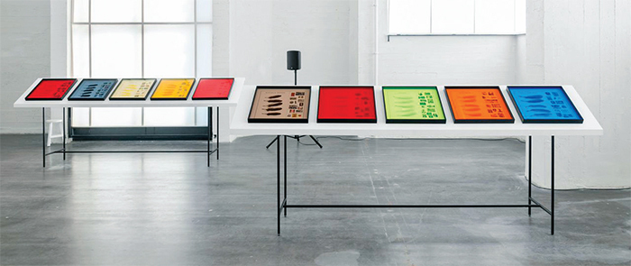 Ana Torfs, [ . . . ] STAIN [ . . . ] (detail), 2012, twenty framed ink-jet prints with mixed media, four tables, two speakers, sound. Installation view.