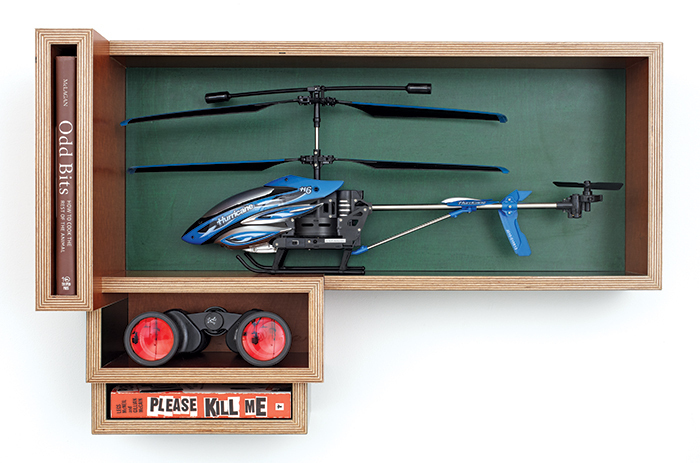 "Jason Kraus, Untitled Object 1, 2014, KoskiDecor, toy helicopter, binoculars, books, 18 × 28 × 9 1/4""."
