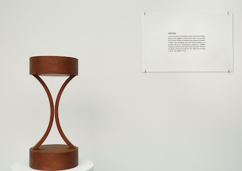 "Iman Issa, Labouring (study 2012), 2012, mahogany, sculpture, text panel under glass, white plinth, 15 1/2 x 12""."