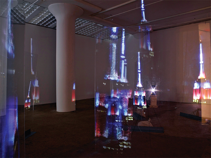 Lutz Bacher, Empire (detail), 2014, Plexiglas, sandbags, two-channel digital video (color, sound, 43 minutes 1 second), dimensions variable. Installation view.