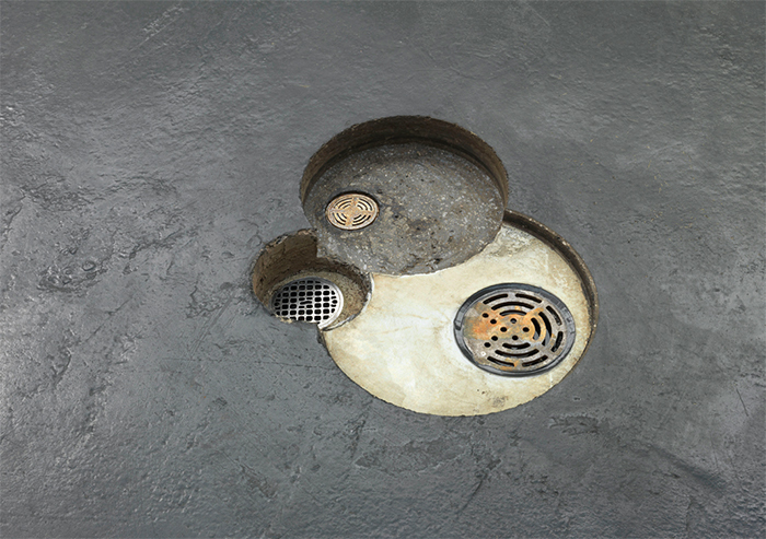 "Renata Lucas, desague (drains), 2015, asphalt, cast iron, steel, stainless steel, PVC, water, 3 1/8 × 17 3/8 × 20 7/8""."