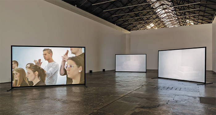 Angelica Mesiti, The Colour of Saying, 2015, three-channel HD video, color, sound, 25 minutes. Installation view.