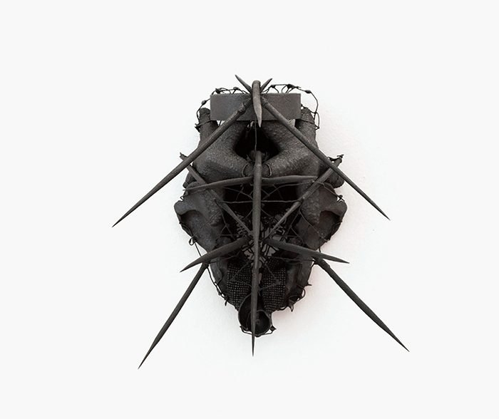 "Tony Orrico, Untitled (mask), 2015, Sri Lankan graphite, porcupine quills, starfish, tape, solder, paper clips, seashell, chicken bones, beads, barro negro, semen, hair, 10 1/4 × 7 × 13""."