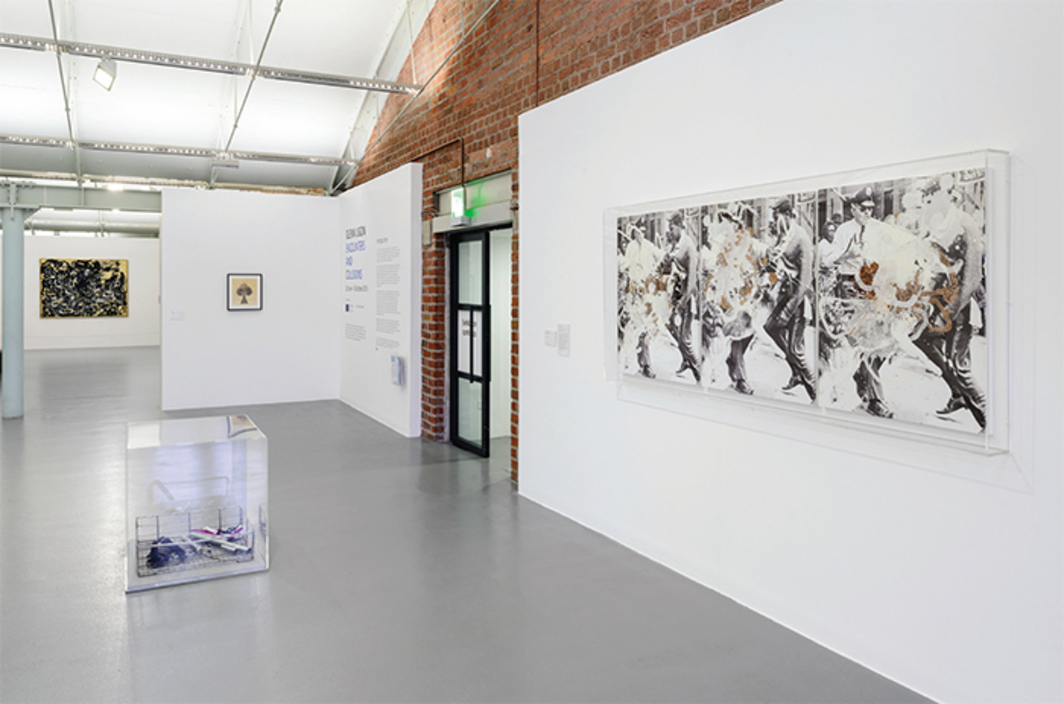 "View of ""Glenn Ligon: Encounters and Collisions,"" 2015, Tate Liverpool, London. Walls, from left: Jackson Pollock, Yellow Islands, 1952; David Hammons, Untitled (Body Print), 1974; Kelley Walker, Black Star Press (Triptych), 2005. Floor: Cady Noland, Pipes in a Basket, 1989. Photo: Roger Sinek."